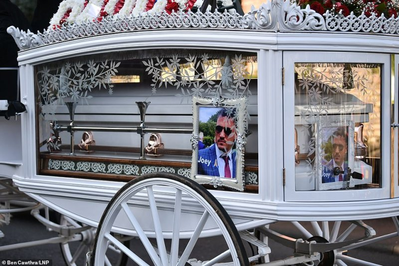 A funeral cortege including two separate white horse-drawn carriages for each of the men's coffins paraded through the town today