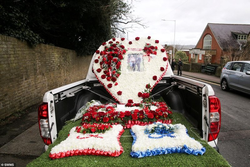 The pick-up truck was covered in huge white, red and blue floral tributes to the two men
