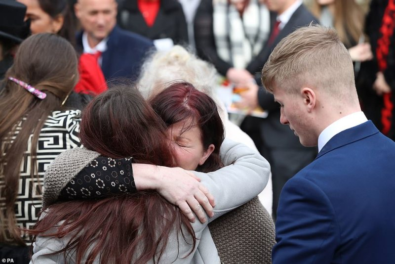 Overcome with grief, mourners are pictured embracing one another outside the church in Kent this morning