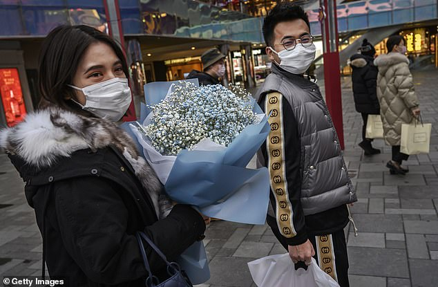 A woman wears a protective mask as she holds flowers given to her on Valentine's Day in Beijing, China