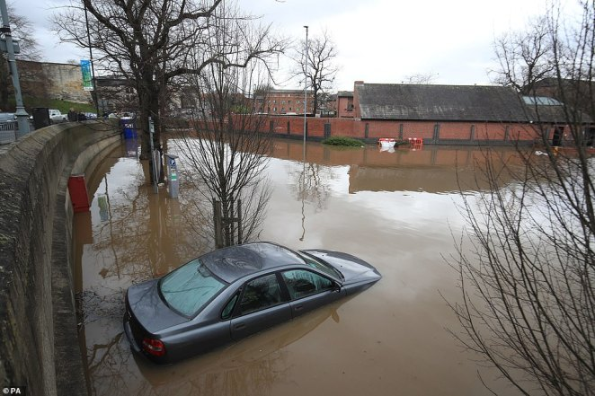 Another vehicle is pictured abandoned in flood water in York where defences are in place to prevent further storm damage