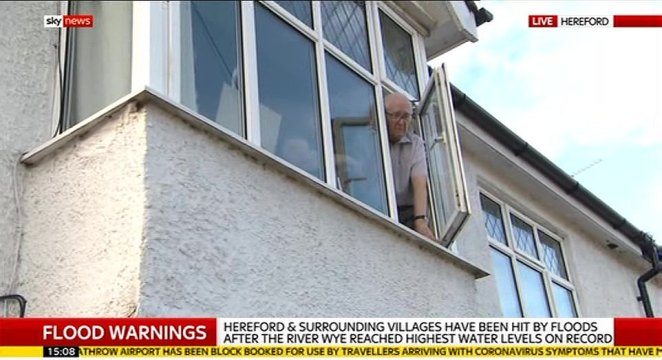 One man is pictured leaning out of his window to speak to Sky News reporter after being confined to the top floor of his house in Hereford due to devastating floods