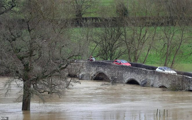 Traffic passes over Teston Bridge on Monday as flood waters rise near Yalding in Kent in the aftermath of Storm Dennis