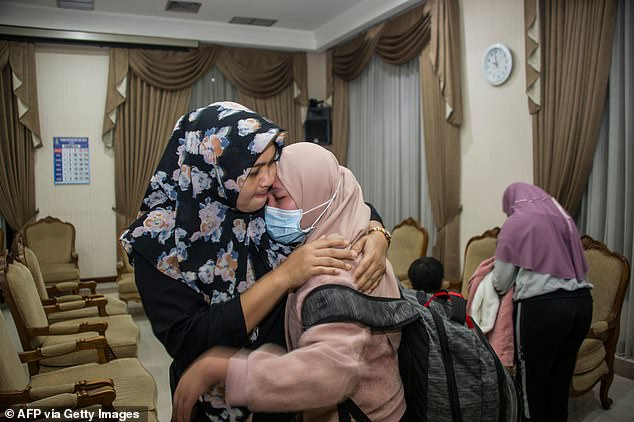 It was an emotional reunion for these women at Indonesian's Juanda International airport on Saturday after a student (wearing face mask) spent time in quarantine following the outbreak