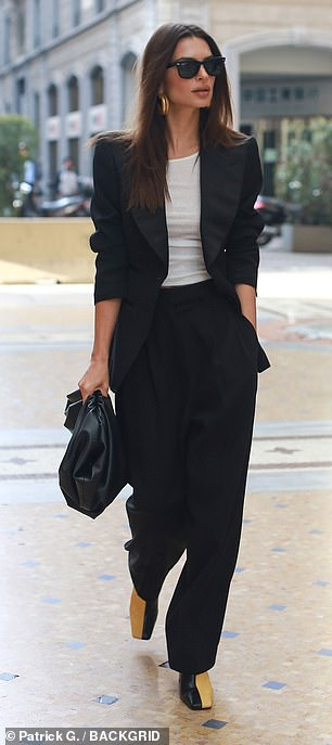Gorgeous: The stylish blazer featured satin lapels and was worn over a white tee, which teased a glimpse of her taut midriff