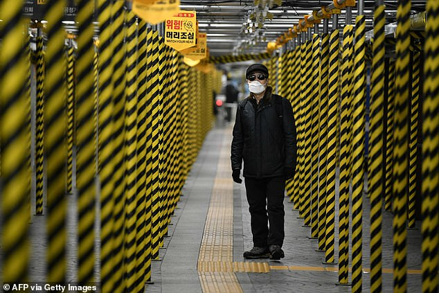 Pictured, a man wearing a face mask at a subway station being renovated in Seoul
