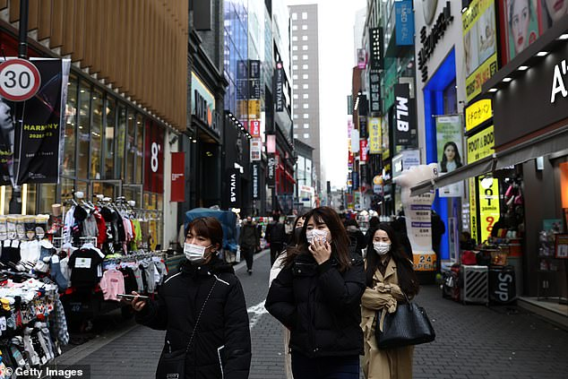 Among the new cases confirmed today, two were in Busan, one of South Korea's largest cities, while one was a solider stationed on Jeju (pictured, people wearing masks)