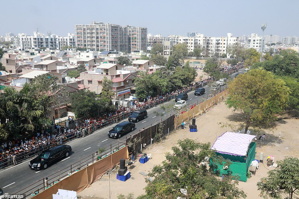 President Trump's motorcade moves through Ahmedabad as Indians lined the streets to cheer him on one said and the other side shows a wall officials built to cover the nation's infamous slums