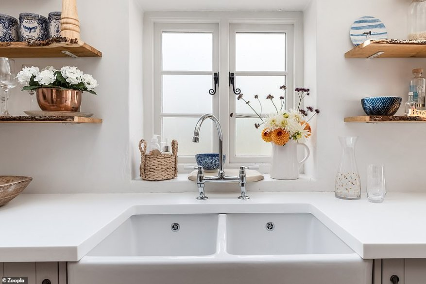 The kitchen is at the rear of the property, where there is a double ceramic sink underneath the window