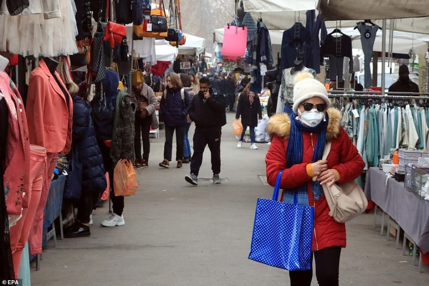 A woman wearing a face mask walks among stalls at street market on Viale Papiniano in Milan, which is typically bustling with midday crowds but is now significantly quieter