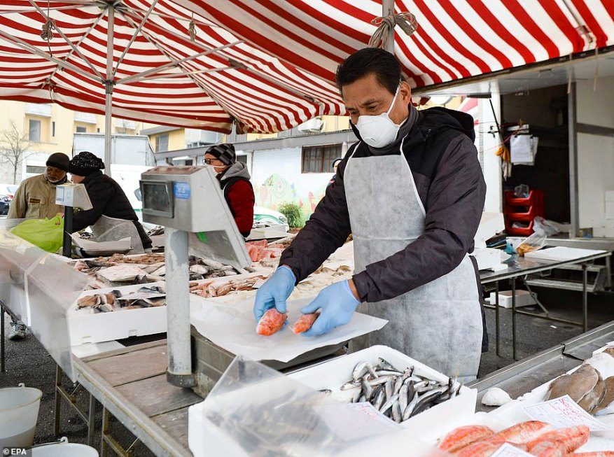 A fish vendor wears a protective face mask at his stall in a local market in the Corvetto district of Milan, Italy