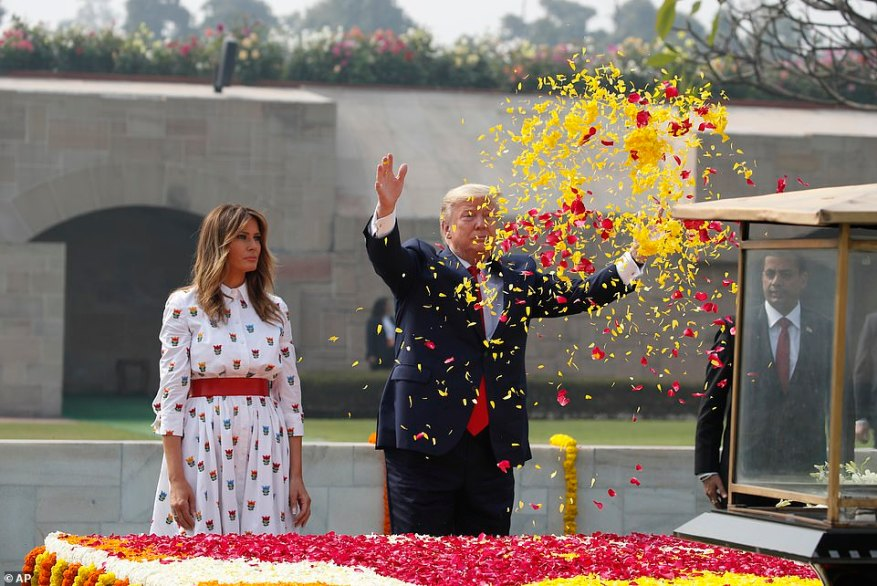 President Donald Trump offers floral respects, with first lady Melania Trump standing beside him, at Raj Ghat, the memorial for Mahatma Gandhi