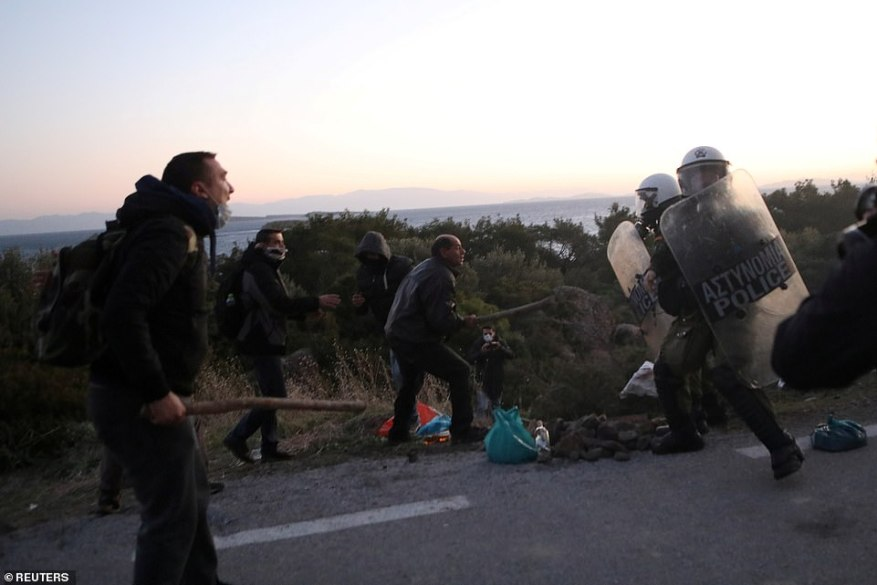 Locals pictured fighting Greek riot police near the village of Karava, Lesbos, early this morning. Regional governor Kostas Moutzouris and West Lesbos mayor Taxiarchis Verros joined the protesters