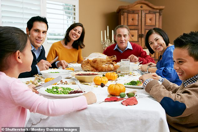 Sitting down to a meal as a family can help everyone to handle the stresses of daily life by talking over recent events or simply enjoy each other's company (file picture)