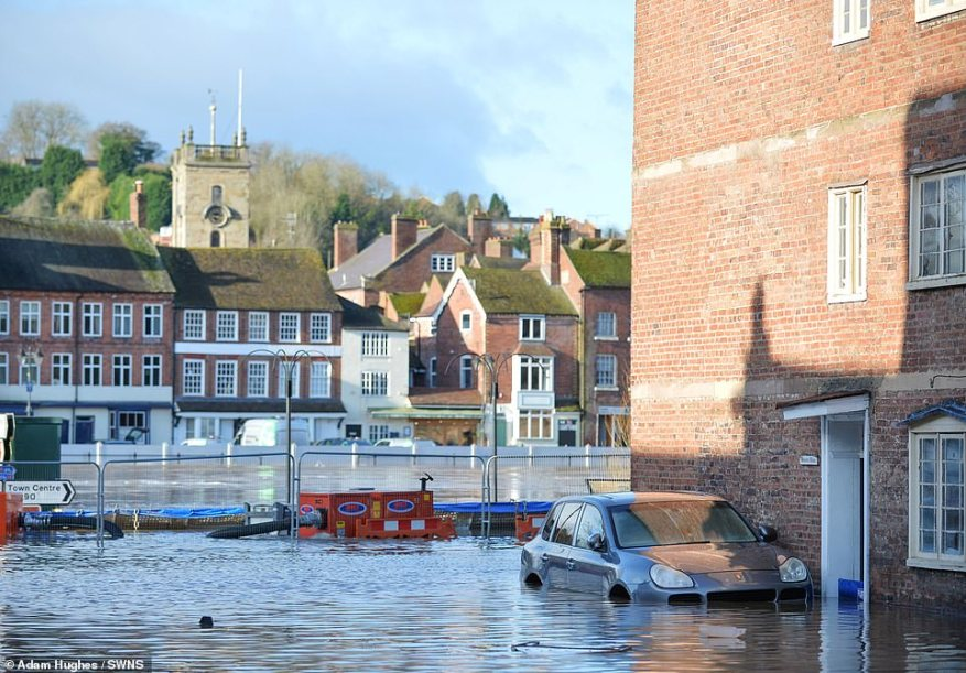 EAST SIDE: Flood barriers fail to hold back the River Severn, in Bewdley, Worcestershire, on one side of the river this morning