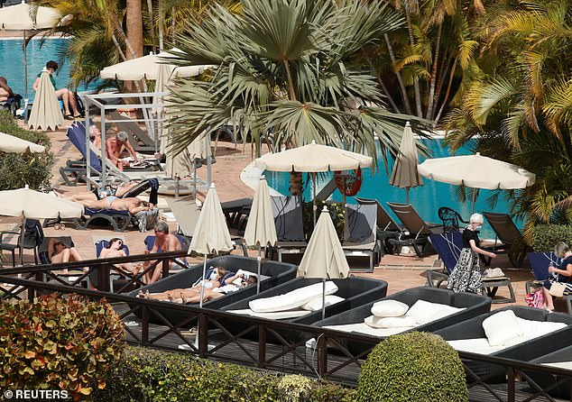 Sunbathing in masks: Tourists lounge by the pool ofH10 Costa Adeje Palace as they settle in for a two-week lockdown after Spanish authorities confirmed a quarantine