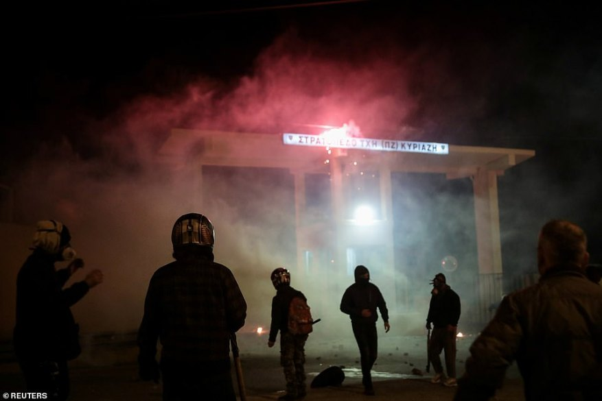 Demonstrators, who oppose the building of a new closed migrant detention centre, clash with riot police outside a military camp housing police officers, near the village of Pagani on the island of Lesbos