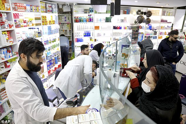 Pharmacists talk with customers at drugstore in downtown Tehran, amid fears the country is running low on medical supplies