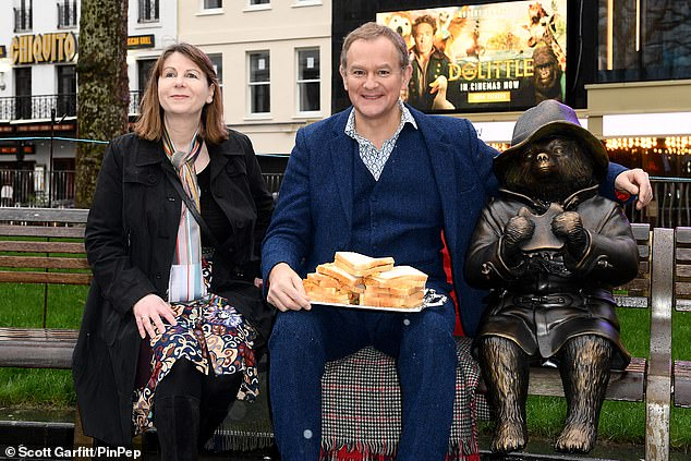 Happy days:Hugh couldn't resist taking the opportunity to tuck into some marmalade sandwiches with none other than Paddington Bear (pictured with authorRosie Alison)