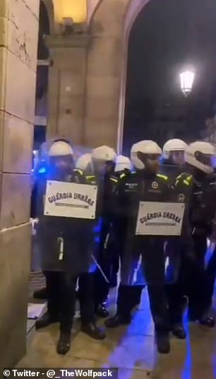 Riot police are seen holding batons during a clash with Wolves fans in Barcelona