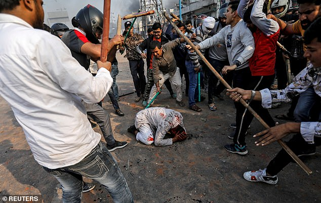 A group of men chanting pro-Hindu slogans, beat Mohammad Zubair, 37, who is Muslim, during protests sparked by a new citizenship law in New Delhi, India on Monday