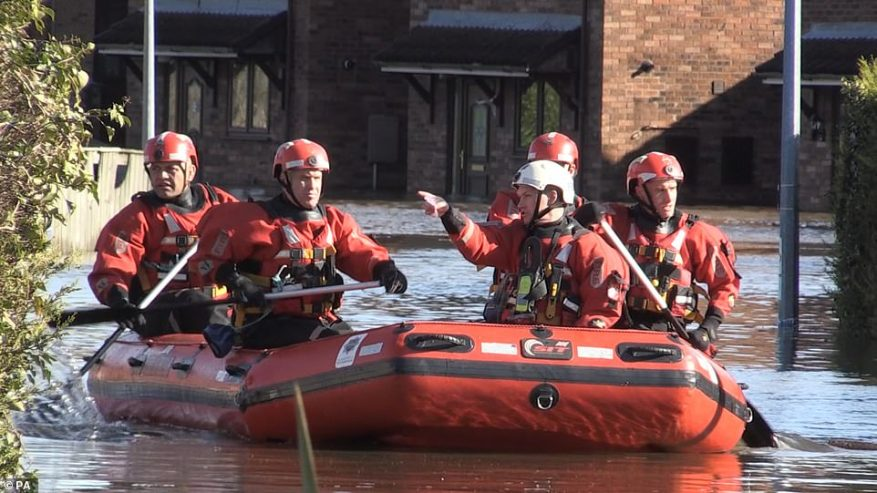 Members of the fire brigade in boats get through floodwater in Snaith, East Riding of Yorkshire, this afternoon