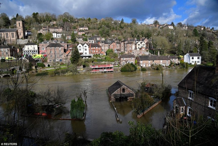 Flooded properties are seen beside the River Severn in Ironbridge today after the river burst its banks in the area