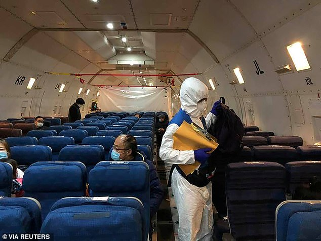 Pictured: Staff from the U.S. embassy walk in a cargo plane, chartered by the U.S. State Department to evacuate Americans and Canadians from China due to the outbreak of novel coronavirus