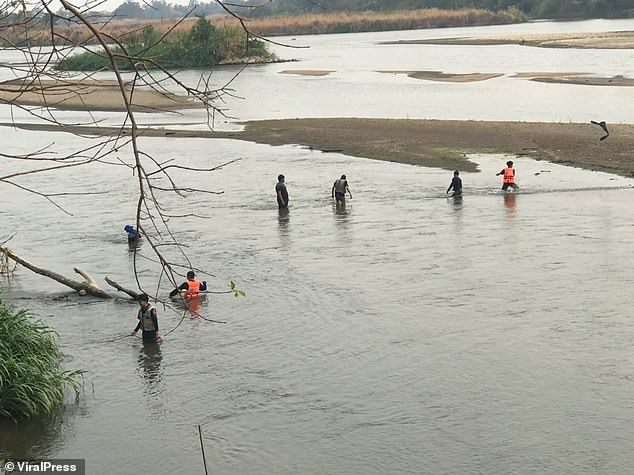 Police pictured searching for the body of Ms Bing. An autopsy has confirmed that her husband died from drowning, Thai police have said
