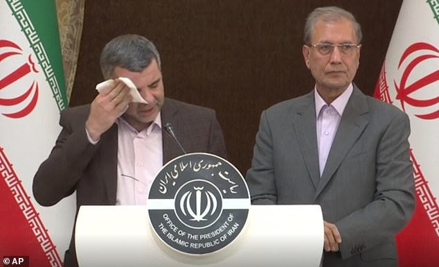 Iraj Harirchi, left, wipes his face during a press briefing with government spokesman Ali Rabiei, in Tehran. The deputy health minister has tested positive for the virus himself