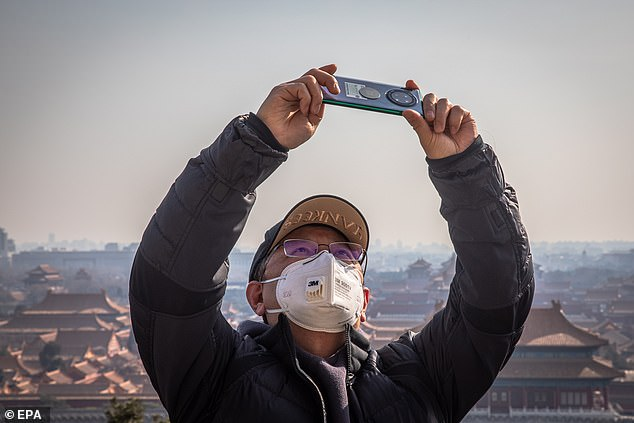 Authorities of major Chinese cities have demanded their citizens wear face masks in public places as mandatory protection to stop the virus from spreading. The picture shows a man wearing a protective face mask taking photos in Jingshan Park, Beijing, on February 25