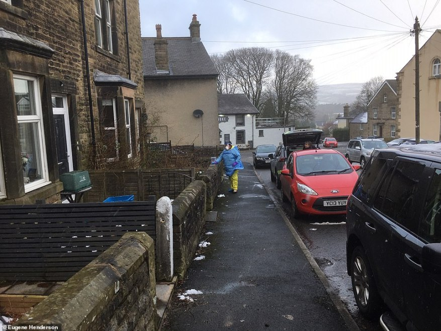 A medic in protective clothes walks to a house close to the scene of the Buxton case yesterday