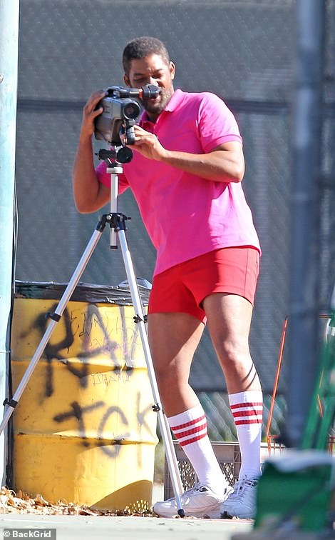 Behind-the-scenes: The 51-year-old leading man looked ready to hit the tennis court, while sporting a hot pink shirt, red shorts and a salt and pepper bread