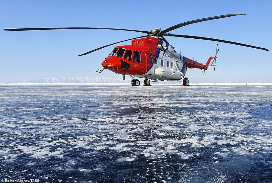 Daredevils took to the frozen surface of the world's deepest lake in a bid to break speed records in a mile-long race. Pictured: A Mil Mi-171A2 medium twin-turbine transport helicopter flying over Lake Baikal
