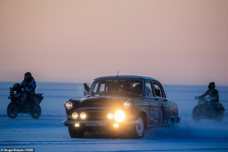 A vintage car raced alongside two motorbikes in the mile-long race along the frozen surface of lake Baikal in Russia