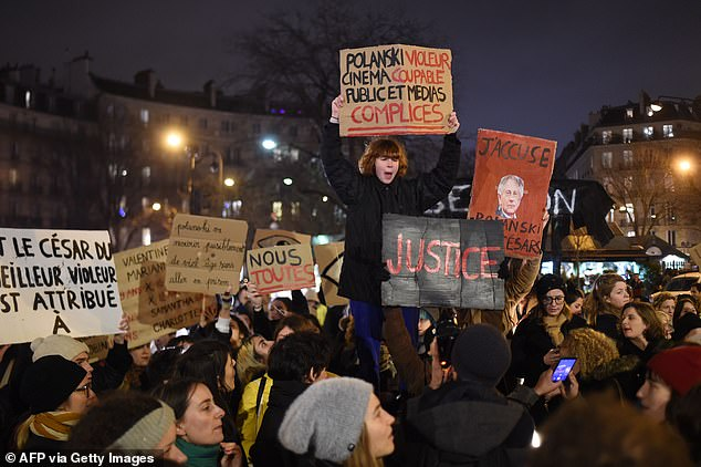 Feminist activists hold signs during a demonstration outside the Salle Pleyel in Paris as guests arrive for the 45th edition of the Cesar Film Awards ceremony on February 28
