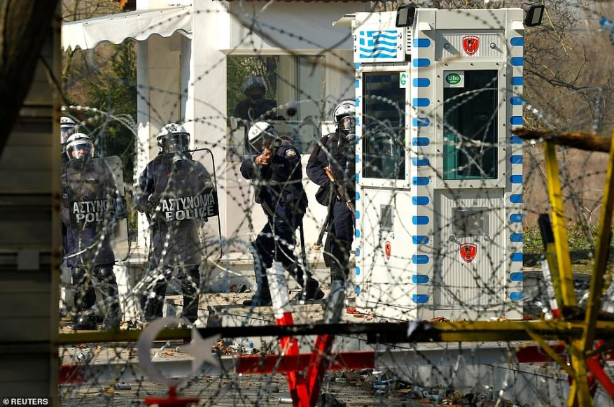 Greek police officers are pictured from Turkey's Pazarkule border crossing with Greece's Kastanies during clashes with migrants, in Edirne, Turkey today