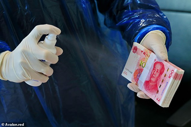 Dirty money: A bank clerk disinfects banknotes in the quarters of Suining Bank. China's central bank has ordered to disinfect cash and destroy cash received from hospitals