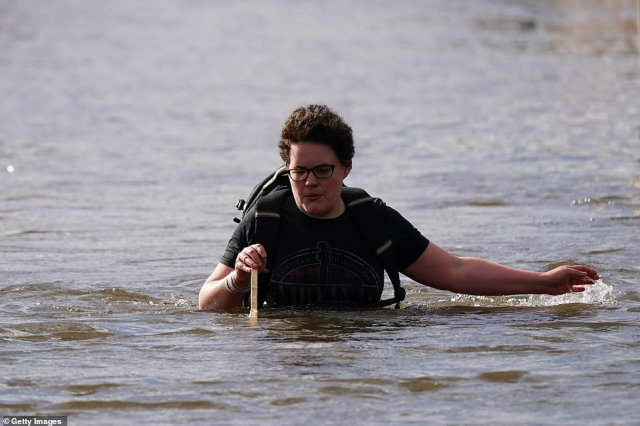 A resident makes her way back through flood water after checking on her property as flooding affects homes and businesses after the River Aire bursts its banks in East Cowick, Yorkshire