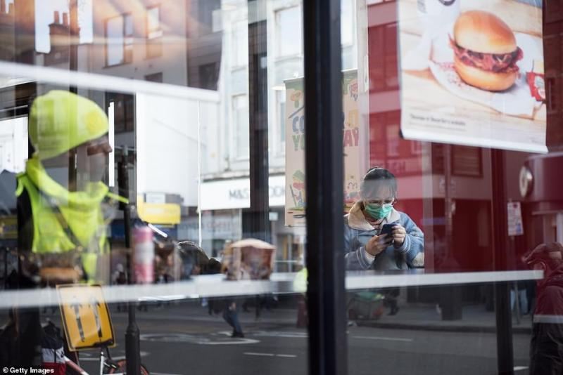 A woman wearing a face mask at a Burger King restaurant in London today. Twelve new cases of coronavirus were diagnosed in  England today