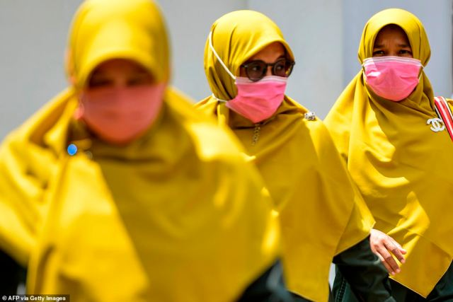 Three women wear face masks as they walk through Banda Aceh, a city on the Indonesian island of Sumatra