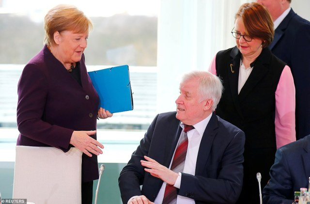 Rejected: German interior minister Horst Seehofer turns away Angela Merkel's offer of a handshake this morning after revealing he had stopped shaking hands over virus fears. Just days ago Merkel had revealed she would not shake hands at an event in her constituency due to the outbreak