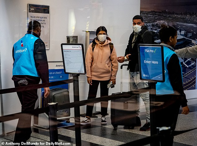 Plane passengers wear surgical masks at LaGuardia Airport, Terminal B in Queens, New York as the first confirmed coronavirus case in New York State is reported