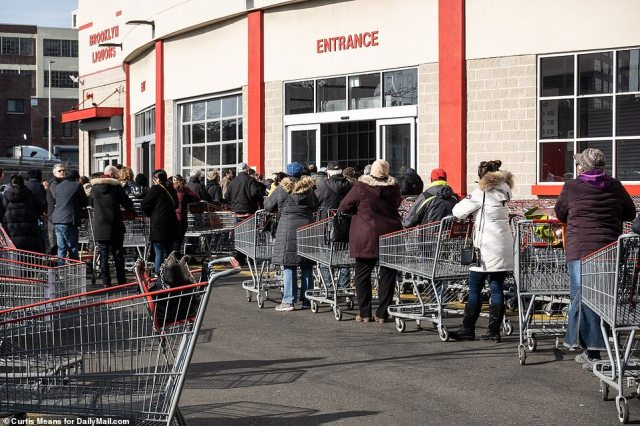 Shoppers at Costco in Brooklyn line up to enter the store on Monday morning to stock up on supplies