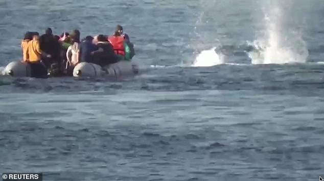The coastguard then appears to shoot at the migrant's vessel, with bullets splashing as they hit the water next to it