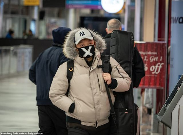 The airline says it is reducing the volume of flights because less people want to travel amid growing concerns about coronavirus. Pictured: A traveller wears a surgical mask at LaGuardia Airport, New York