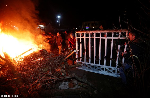 Demonstrators set fire and erect a barricade as they protest the arrival of a plane carrying evacuees from coronavirus-hit China's Hubei province