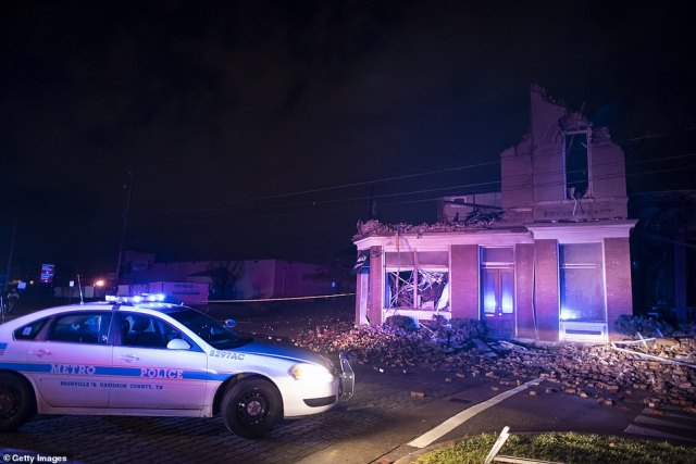A police car in front of a wrecked building housing a dry cleaning business in Nashville, Tennessee, in the early hours of this morning