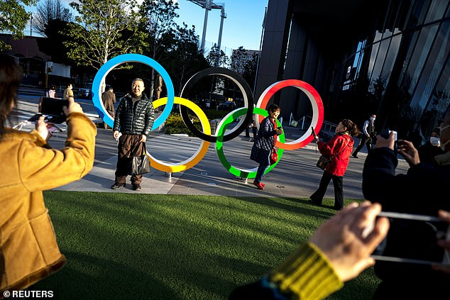 People pose for photographs in front of the Olympic rings at the Japan Olympic Museum in Tokyo last month, only five months before the Games are due to begin