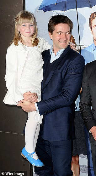 Matilda (pictured, with her father Kris) was eight when she caught fire as her outfit went up in flames due to a nearby candle and Claudia has revealed it still haunts her